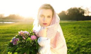 草地上拿着手捧花的新娘摄影图片