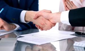 商务谈判桌上握手场景特写摄影图片