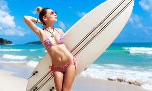 抱着冲浪板的泳装美女人物摄影图片