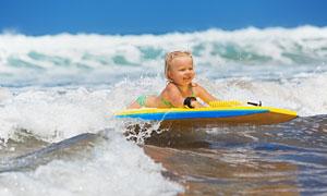 海边浅水区玩冲浪的小女孩高清图片