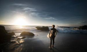 站在沙滩上准备冲浪的男子摄影图片