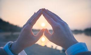 心形手势中的落日美景摄影图片