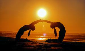 傍晚在沙滩上做瑜伽的人摄影图片