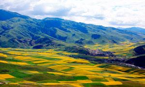 山坡下的村庄和农田摄影图片