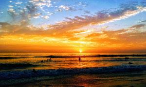 夕阳下在海边玩水的游客摄影图片