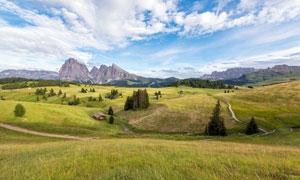 蓝天白云下的山坡草地美景摄影图片