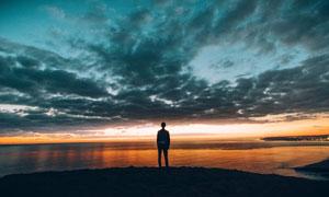 站在山顶看海边夕阳的男人摄影图片