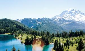 雪山下美丽山林和湖泊摄影图片