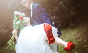 逆光下抱着新娘的新郎摄影图片