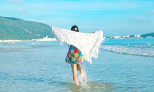 海边披着围巾沙滩上奔跑的美女摄影图片
