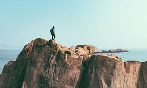 站在海边悬崖上的男人摄影图片