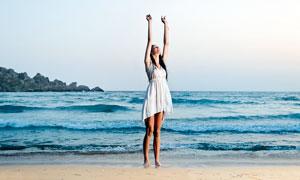 海边沙滩上举着双手的美女摄影图片