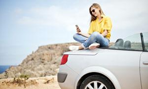 坐在汽车上玩手机的美女摄影图片