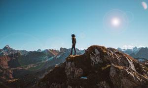 攀登到山顶的女子摄影图片