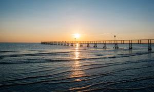 夕阳下海边栈桥摄影图片