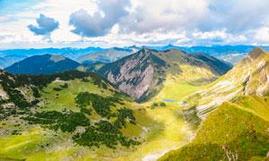 蓝天白云下连绵的山峰摄影图片