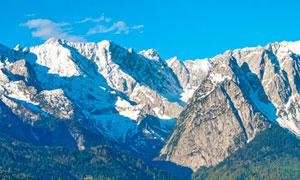 蓝天下的雪山全景图摄影图片