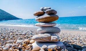 沙滩上叠起的鹅卵石特写摄影图片
