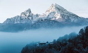 清晨雪山下雾气中的房屋摄影图片
