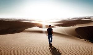 沙漠中行走的男人摄影图片