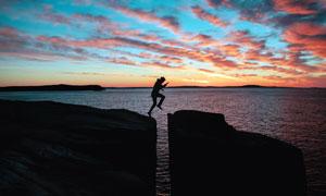 傍晚在海边悬崖上跨越的人物摄影图片