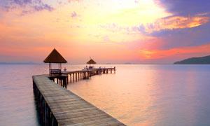 夕阳下的海边栈桥高清摄影图片