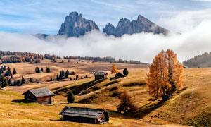 秋季大山下的房屋和山林景观摄影图片