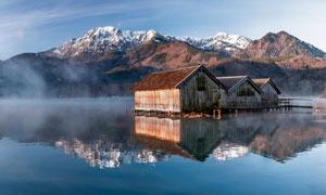 雪山脚下湖泊中的小木屋摄影图片
