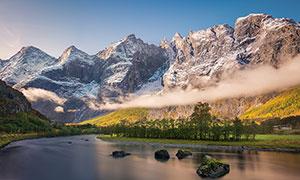 雪山脚下平静的河流摄影图片