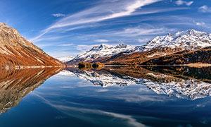 蓝天白云下的雪山和湖泊倒影摄影图片