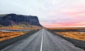 傍晚田野上的公路景观摄影图片