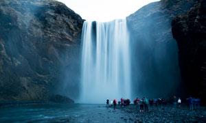 悬崖下观看瀑布的游客摄影图片