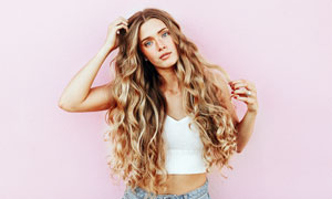 摸着头发的卷发美女摄影图片