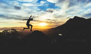夕阳下在山顶跳跃的男人摄影图片