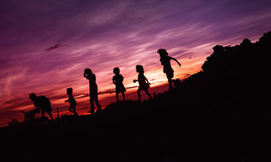 傍晚山坡上一家人剪影摄影图片