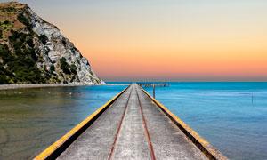 傍晚通向海边码头的栈桥摄影图片