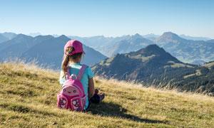 坐在山坡草地上看风景的小女孩摄影图片
