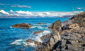 蓝天下的海边岩石和礁石摄影图片