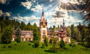 陽光下樹林中的歐式城堡攝影圖片