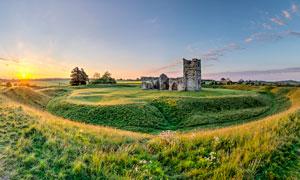 夕阳下的草地和建筑遗址摄影图片