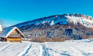 山腳下的積雪和小木屋攝影圖片
