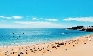 海邊在沙灘上度假的游客攝影圖片