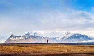 雪山下的草原和游客攝影圖片
