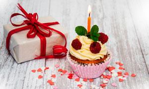 点燃蜡烛的小杯蛋糕和生日礼物摄影图片
