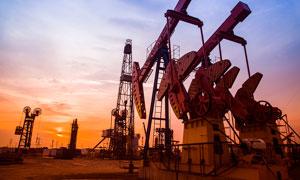 夕阳下油田中正在工作的抽油机摄影图片
