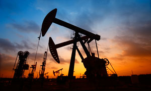 夜幕降临下的油田抽油机剪影摄影图片