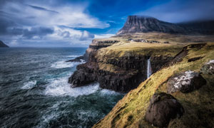 海邊的懸崖和小瀑布攝影圖片
