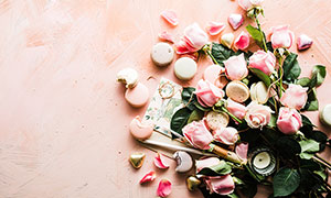 地上擺放的馬卡龍和玫瑰花攝影圖片