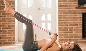 仰臥著做彈力繩鍛煉的美女高清圖片