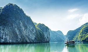 大山下湖泊中的游船攝影圖片